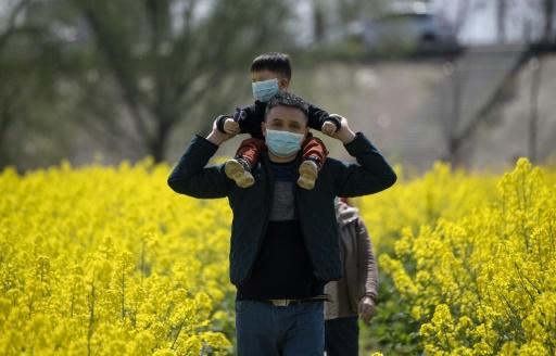 People wearing face masks walk through a rapeseed farm used to produce canola oil in China's central Jiangxi province that borders Hubei province, the epicenter of the country's COVID-19 coronavirus outbreak
