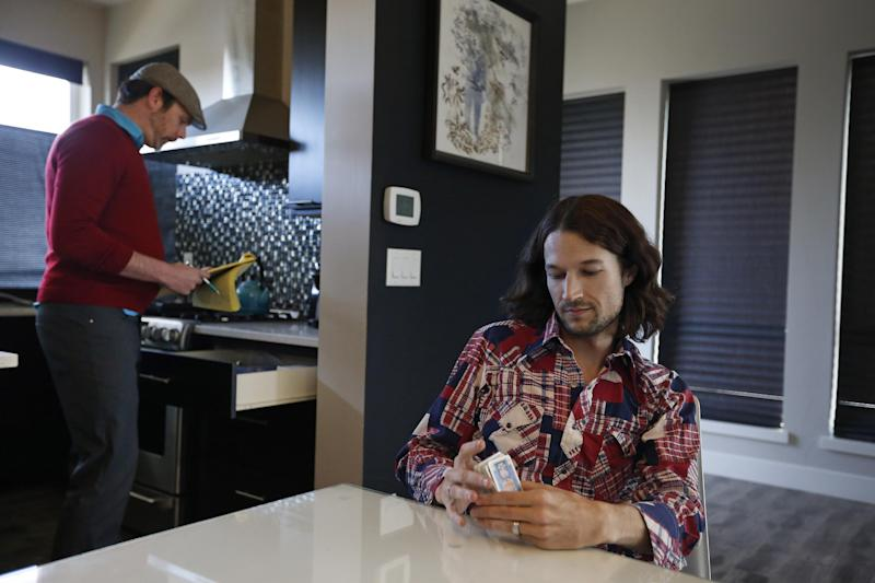 In this March 13, 2014 photo, Charlie Craig, left, and his husband Dave Mullins prepare to play cards while hanging out together after a work day, at their home in Westminster, Colo. The couple filed a legal complaint with the Colorado Civil Rights Commission against a Denver-area baker who refused to make a wedding cake for the two men, based on his religious beliefs. The baker, Masterpiece Cakeshop owner Jack Phillips, is appealing a ruling by a judge in December 2013 which upheld the complaint, and orders the baker to serve gay couples despite his religious beliefs or face fines. (AP Photo/Brennan Linsley)