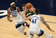 Milwaukee Bucks' Pat Connaughton, center, drives between Minnesota Timberwolves' Josh Okogie, left, and Juancho Hernangomez in the first half of an NBA basketball game Wednesday, April 14, 2021, in Minneapolis. (AP Photo/Jim Mone)