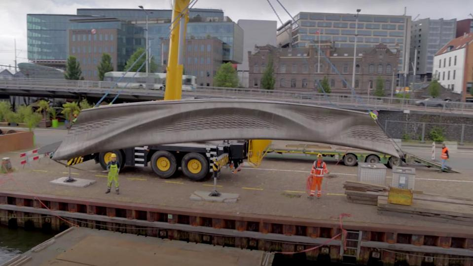 Construction workers using a crane to hoist a 3D-printed bridge in Amsterdam.