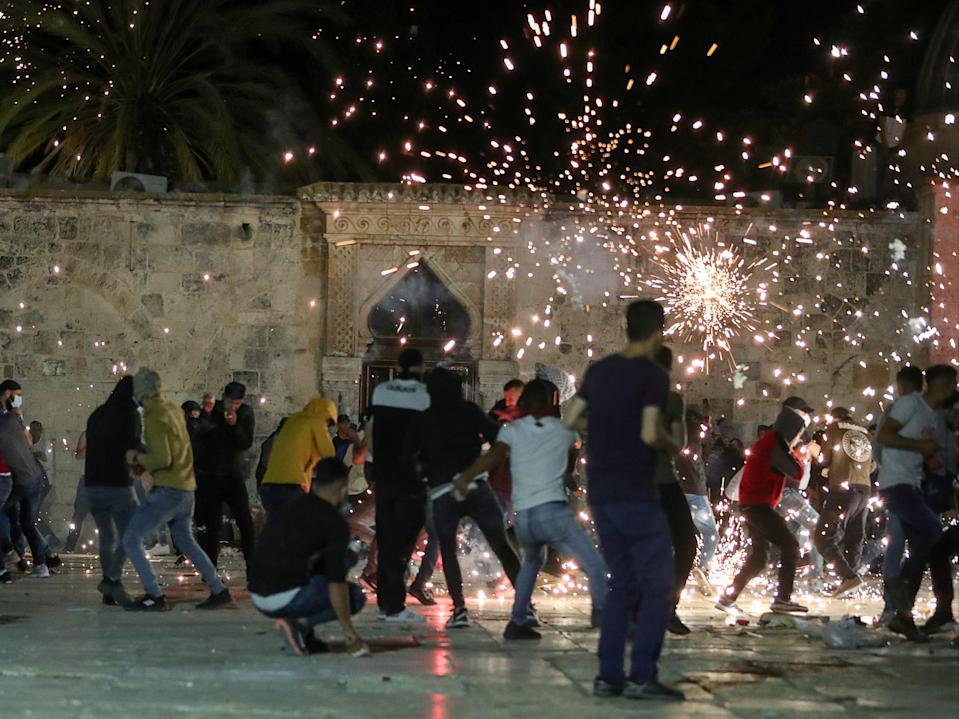 Palestinians react as Israeli police fire stun grenades during clashes at the compound that houses Al-Aqsa Mosque (REUTERS)