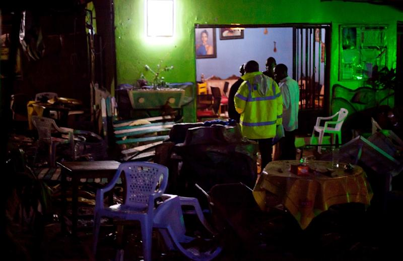 Ugandan police inspect the destroyed Ethiopian Village restaurant in Kampala after twin bomb blasts late on July 11, 2010 tore through crowds of football fans watching the World Cup final