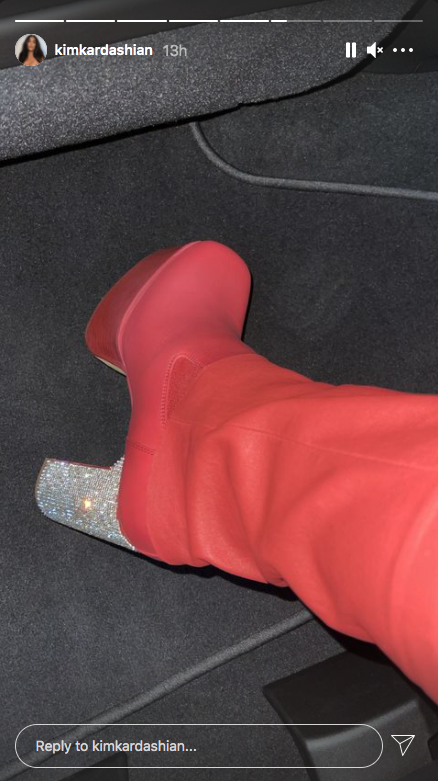 Kim Kardashian takes a picture of her red boots with sparkly heels at Kanye West's album listening event