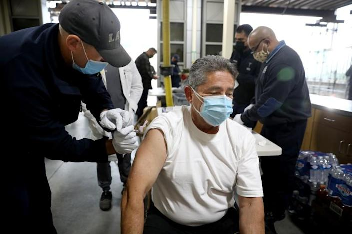 LOS ANGELES, CA - DECEMBER 28: Matthew Kovar, left, Los Angeles Fire Department (LAFD) firefighter paramedic, administers a Moderna COVID-19 vaccination to Gabriel Orona, LAFD fire inspector, at LAFD Station 4 on Monday, Dec. 28, 2020 in Los Angeles, CA. Mayor of Los Angeles Eric Garcetti and Ralph M. Terrazas, Fire Chief of the Los Angeles Fire Department (LAFD), were there to observe the rollout of the vaccination program. (Gary Coronado / Los Angeles Times)