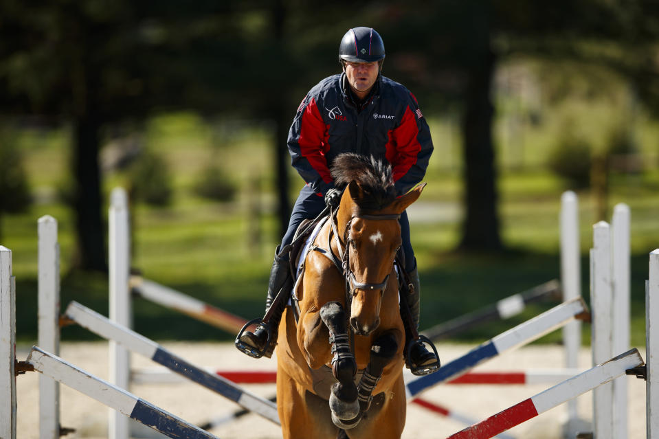 FILE - Phillip Dutton rides Z through a series of jumps while training at his farm in West Grove, Pa., in this Thursday, April 2, 2020, file photo. The roster released by the U.S. Olympic and Paralympic Committee for the Tokyo Games includes 329 women and 284 men. Swimmer Katie Grimes is the youngest U.S. Olympian at 15, while equestrian Phillip Dutton is the oldest at 57. (AP Photo/Matt Slocum, File)