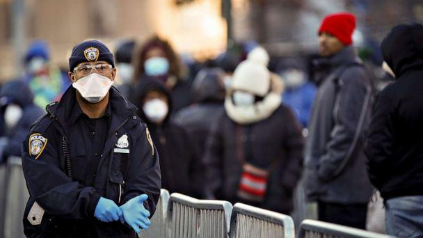 PHOTO: A New York City Police officer puts on gloves as people wait in line to be tested for COVID-19, outside Elmhurst Hospital Center in the Queens borough of New York City, March 26, 2020. (Stefan Jeremiah/Reuters)