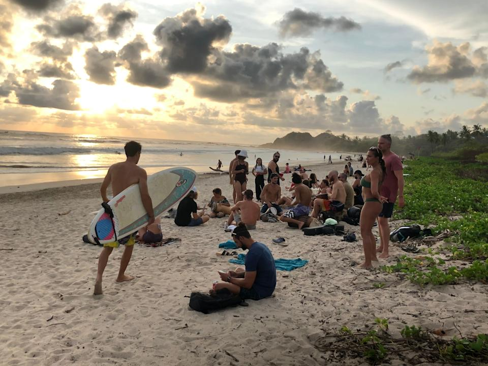 Visitors gather to watch the sunset April 19, 2021, in Playa Guiones, a surfing destination located near the town of Nosara, Costa Rica. U.S. travelers need to carry proof of vaccination to enter the country.