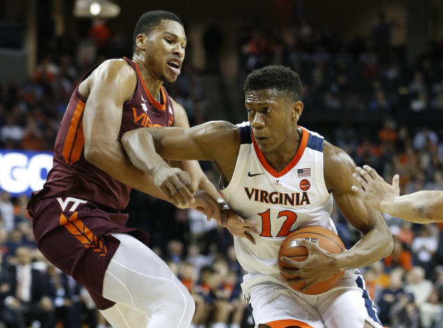 Virginia Tech forward Kerry Blackshear Jr. , left, tries to block Virginia guard De'Andre Hunter (12) during the first half of an NCAA college basketball game in Charlottesville, Va., Tuesday, Jan. 15, 2019. (AP Photo/Steve Helber)