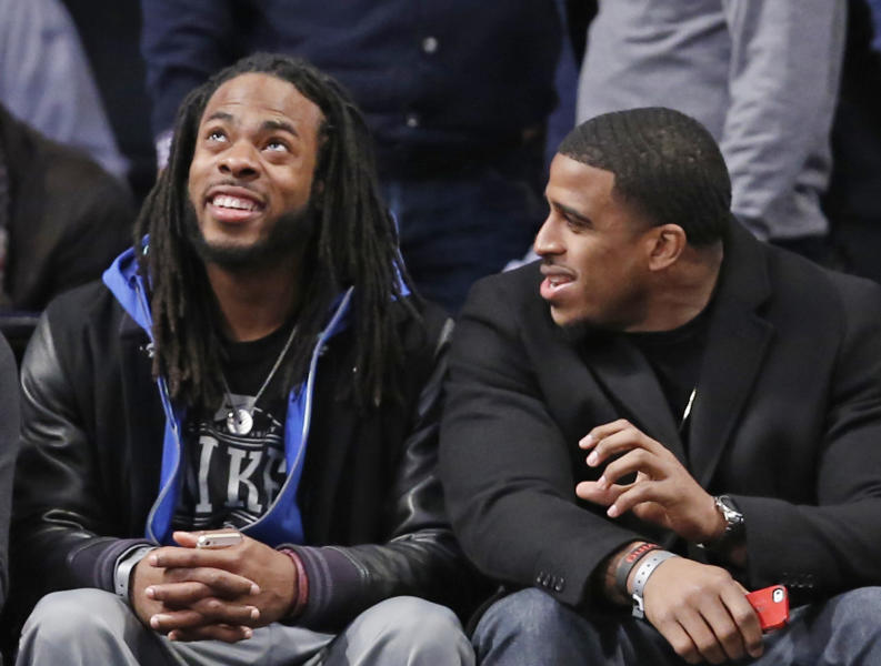 Seattle Seahawks cornerback Richard Sherman, left, and linebacker Bobby Wagner watch the Toronto Raptors in the first half of an NBA basketball game against the Brooklyn Nets at the Barclays Center, Monday, Jan. 27, 2014, in New York. (AP Photo/Kathy Willens)