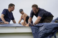 Bob Primeaux, right, works with his son Robbie in the aftermath of Hurricane Laura on a roof that was damaged on Friday, Aug. 28, 2020, in Homewood, La. (AP Photo/Gerald Herbert)