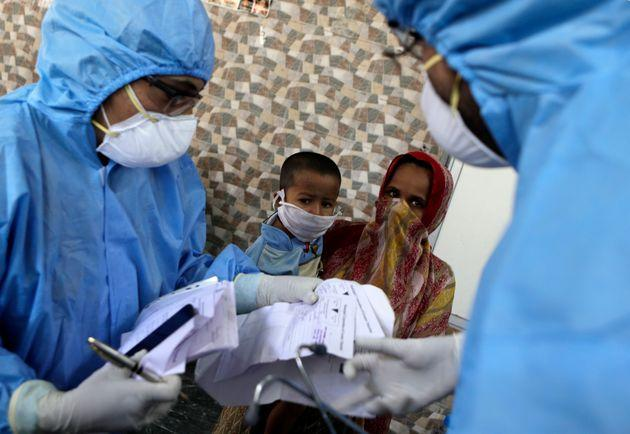 Doctors interact with people at a slum area during lockdown to control the spread of the new coronavirus in Mumbai, India, Tuesday,
