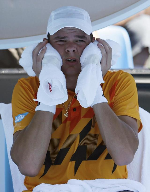 Milos Raonic of Canada cools himself with an ice pack during a break in his first round match against Daniel Gimeno-Traver of Spain at the Australian Open tennis championship in Melbourne, Australia, Tuesday, Jan. 14, 2014. (AP Photo/Aijaz Rahi)