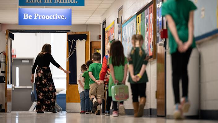 Socially distanced, masked students line up at Medora Elementary School in Louisville, Ky., on March 17. (Jon Cherry/Getty Images)