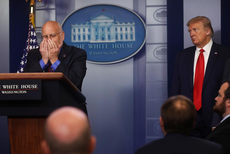 U.S. President Donald Trump watches as Centers for Disease Control (CDC) Director Robert Redfield physically demonstrates the need for the use of face masks by the public as part of safety protocols during the daily coronavirus task force briefing at the White House in Washington, U.S., April 22, 2020. REUTERS/Jonathan Ernst