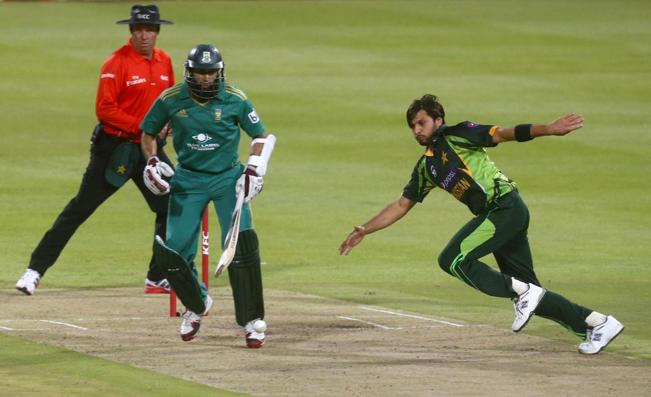 Pakistan's Shahid Afridi chases the ball as South Africa's Hashim Amla looks on during their second Twenty20 cricket match in Cape Town, November 22, 2013. REUTERS/Mike Hutchings (SOUTH AFRICA - Tags: SPORT CRICKET)
