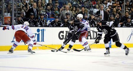 Jun 13, 2014; Los Angeles, CA, USA; Los Angeles Kings right wing Justin Williams (14) controls the puck between New York Rangers right wing Derek Dorsett (15) and defenseman Marc Staal (18) during the first period in game five of the 2014 Stanley Cup Final at Staples Center. Gary A. Vasquez-USA TODAY Sports