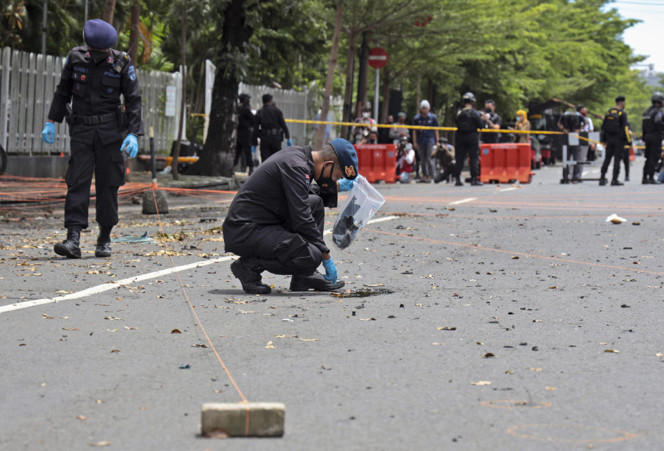 Members of police bomb squad search the area around the site of Sunday's suicide bomb attack at the Sacred Heart of Jesus Cathedral for evidence, in Makassar, South Sulawesi, Indonesia, Monday, March 29, 2021. Two attackers believed to be members of a militant network that pledged allegiance to the Islamic State group blew themselves up outside the packed Roman Catholic cathedral during a Palm Sunday Mass on Indonesia's Sulawesi island, wounding a number of people, police said. (AP Photo/Yusuf Wahil)