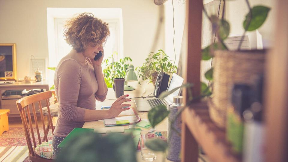 Woman working from home, using phone, sitting on the chair and writing into the book.