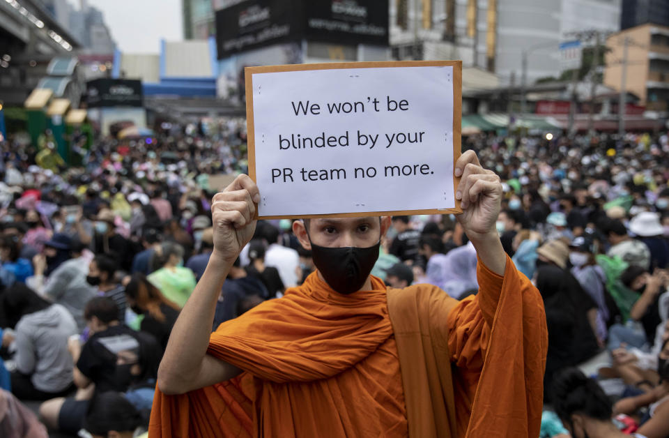 A Buddhist monk, supporter of pro-democracy movement, displays a placard during a protest rally at an intersection in Bangkok, Thailand, Sunday, Oct. 18, 2020. Pro-democracy activists in Thailand launched their fifth straight days of protests on Sunday, scheduling demonstrations not just in the capital but also at several other locations around the country. (AP Photo/Gemunu Amarasinghe)