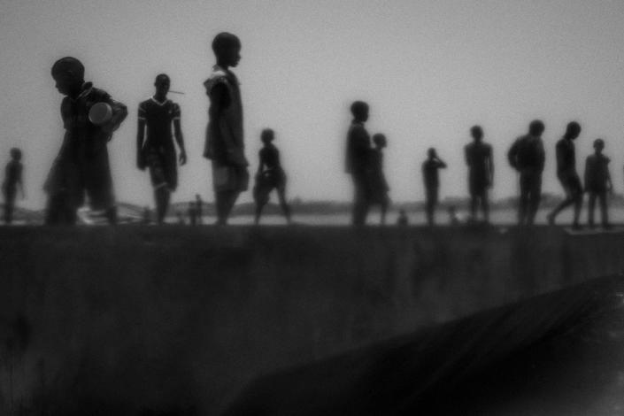 <p>Runaway talibes stand on the banks of the Senegal River in Saint Louis, north of Senegal, May 20, 2015. Saint Louis is known as Talibe City. Saint Louis is a city of small proportions compared to Dakar but has a large number of talibes, so many of them choose the streets instead of daaras. (Photograph by Mario Cruz) </p>