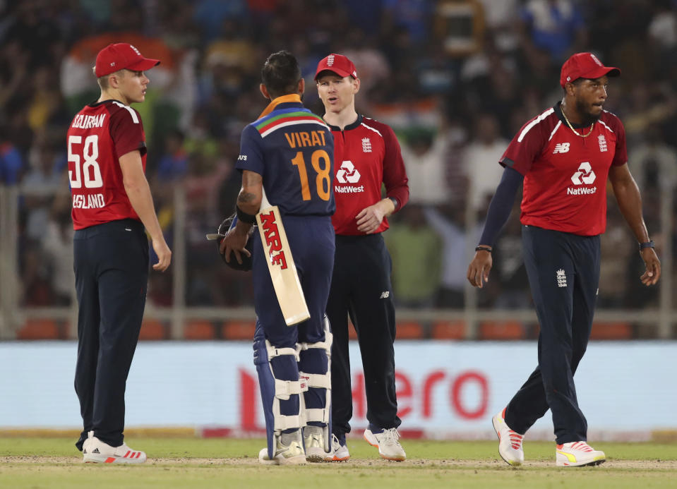 India's captain Virat Kohli, second left, shakes hands with England's captain Eoin Morgan after their win in the second Twenty20 cricket match between India and England at Narendra Modi Stadium in Ahmedabad, India, Sunday, March 14, 2021. (AP Photo/Aijaz Rahi)