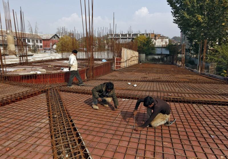 Migrant workers fasten iron rods together at the construction site of a parking lot in Srinagar