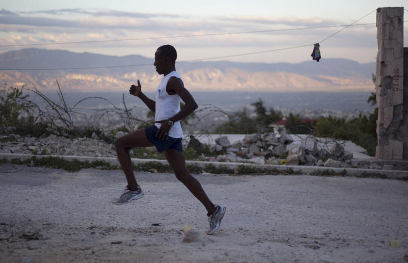 In this Jan. 7, 2013 photo, Astrel Clovis, a 42-year-old marathon runner, trains in the early morning in Petionville, a suburb of Port-au-Prince, Haiti.  Like virtually all Haitians in the capital of 3 million, the runner's life was disrupted by the catastrophic earthquake on Jan. 12, 2010. But a month later he was back on the streets, resuming his routine along with the rest of the country. Six days a week, the rail-thin athlete sets off at daybreak. Clovis has run the hills and streets of Port-au-Prince for the past 10 years. He decided to take the sport seriously after he entered a race in downtown Port-au-Prince on a whim - and won. (AP Photo/Dieu Nalio Chery)