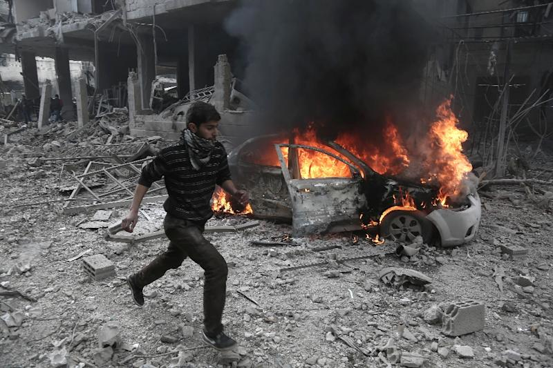 A man runs past a burning car after a reported bombardment by Syrian and Russian forces in the rebel-held area of Hammuriyeh in Eastern Ghouta on January 6, 2018 (AFP Photo/ABDULMONAM EASSA)