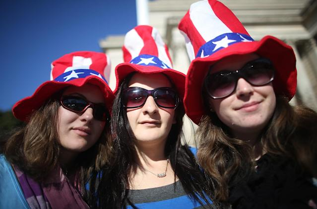 WASHINGTON, DC - JANUARY 20: (L to R) Bek Russell, Jane Heard and Emma Llewellyn, tourists from Australia, pose while sporting Uncle Sam hats as Washington prepares for U.S. President Barack Obama's second inauguration on January 20, 2013 in Washington, DC. One day before the public inaugural ceremony at the U.S. Captiol on January 21, Obama was officially sworn in for his second term during a private ceremony surrounded by friends and family in the Blue Room of the White House. (Photo by Mario Tama/Getty Images)