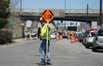 In this Thursday, April 29, 2021, photograph, a traffic worker advises motorists headed northbound along York Street as construction continues on what will become Interstate 70 north of downtown Denver. The elevated roadway that has served as Interstate 70 will be demolished as part of the 10-mile-long project, which will cost $1.2 billion by completion by winter 2022. (AP Photo/David Zalubowski)