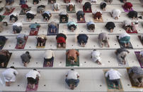 Muslims pray spaced apart as a precaution against the coronavirus outbreak during an Eid al-Adha prayer at Zona Madina mosque in Bogor, Indonesia, Tuesday, July 20, 2021. Muslims across Indonesia marked a grim Eid al-Adha festival for a second year Tuesday as the country struggles to cope with a devastating new wave of coronavirus cases and the government has banned large gatherings and toughened travel restrictions. (AP Photo/Tatan Syuflana)