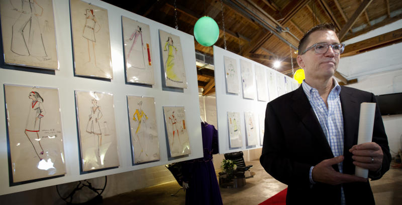 In this Monday, Dec. 30, 2013 photo, auctioneer Rico Baca stands beside some of Karl Lagerfeld's drawings that will be sold in West Palm Beach, Fla. The signature of designer Lagerfeld is adding an extra splash of glamour to a collection of fashion sketches up for auction in Florida. The half-century-old archive from the House of Tiziani in Rome will be sold Jan. 11, 2014, at Palm Beach Modern Auctions. In the 1960s, Tiziani designed movie costumes and clothing for Elizabeth Taylor and other celebrities. (AP Photo/J Pat Carter)