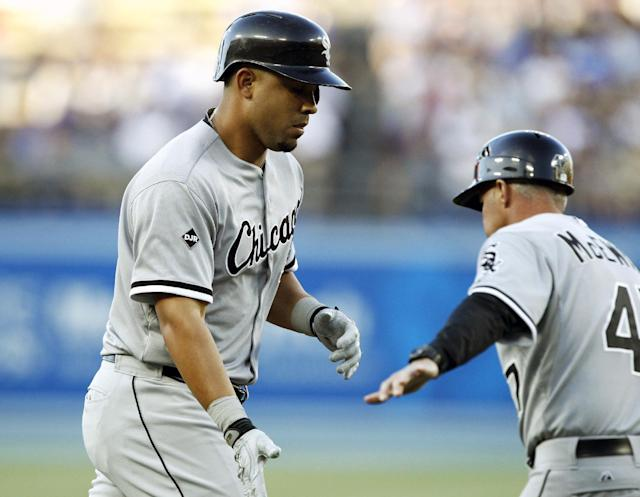 Chicago White Sox third base coach Joe McEwing, right, congratulates Jose Abreu rounding third after hitting a two-run home run against the Los Angeles Dodgersin the first inning of a baseball game on Tuesday, June 3, 2014 in Los Angeles. (AP Photo/Alex Gallardo)