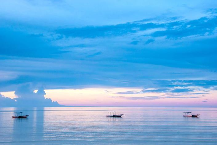 Endless ocean blue water with three fishing boats at sunset, very calming