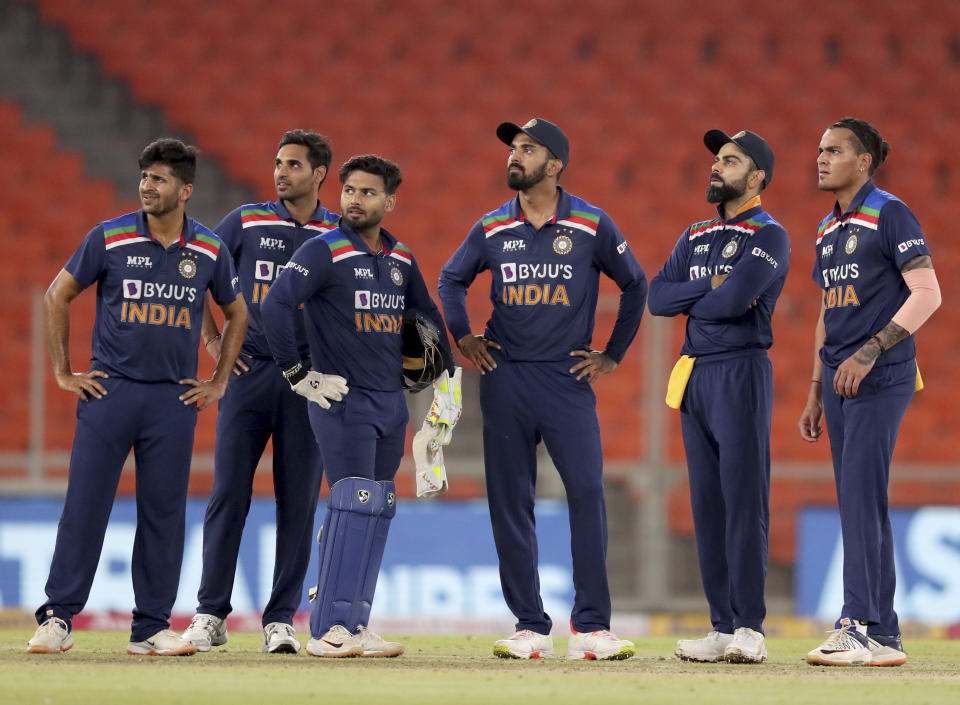 Rahul Chahar (R) and teammates watch the replay of the dismissal of Dawid Malan in Ahmedabad. (AP Photo/Ajit Solanki)