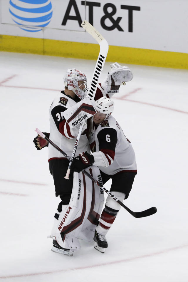 Arizona Coyotes goalie Darcy Kuemper, left, celebrates with defenseman Jakob Chychrun after the Coyotes defeated the Chicago Blackhawks 4-3 in a shootout of an NHL hockey game Sunday, Dec. 8, 2019, in Chicago. (AP Photo/Nam Y. Huh)