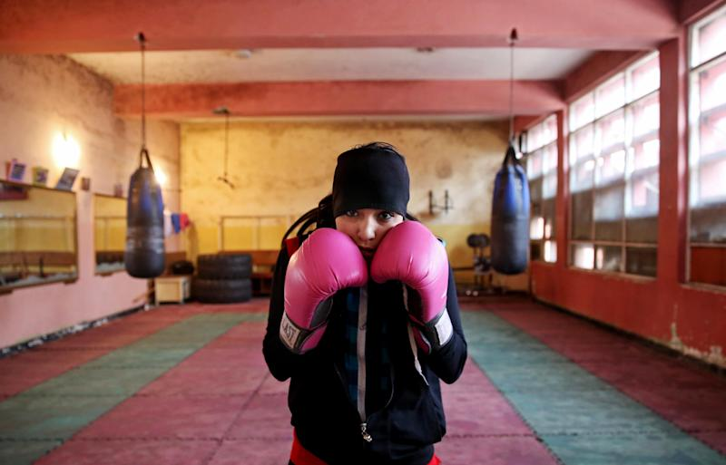 In this Wednesday, March, 5, 2014 photo, an Afghan female boxer pauses during a practice session at the Kabul Stadium boxing club. The Afghanistan National Olympic Committee boxing club has fewer than a dozen women and little money for them. Previously nongovernmental organizations supported them. At that time there were 25 young women who received a salary the equivalent of $100 per month and transportation to and from the Kabul Stadium where they train. (AP Photo/Massoud Hossaini)