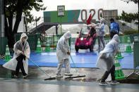 Staff wipe off rain water from the competition site prior to the women's triathlon competition at the 2020 Summer Olympics on Tuesday, July 27, 2021, in Tokyo, Japan. (AP Photo/Eugene Hoshiko)