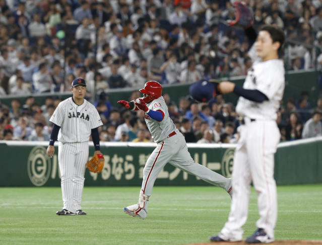 MLB All-Star Carlos Santana, center, of the Philadelphia Phillies rounds bases after hitting a three-run home-run off All Japan's pitcher Kakeru Narita, right, in the 5th inning of Game 1 of their All-Stars Series baseball at Tokyo Dome in Tokyo, Friday, Nov. 9, 2018. (AP Photo/Toru Takahashi)