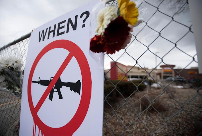A sign calls for gun control at a memorial outside King Soopers for the victims of a mass shooting at the market in Boulder, Colo., in March.