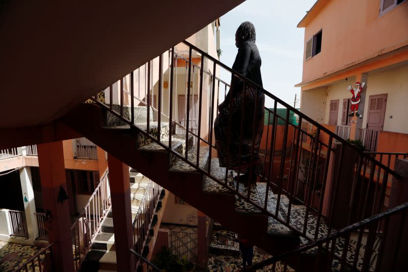 Woman who said she was raped twice, walks up the stairs at La Maison Rose in Dakar