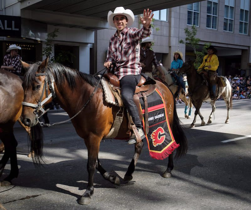 <p>Johnny Gaudreau of the Calgary Flames waves to the crowd as he rides a horse during the Calgary Stampede parade in Calgary on July 6, 2018. Photo from The Canadian Press. </p>