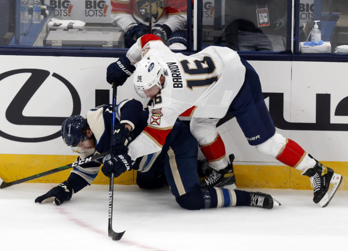 Florida Panthers forward Aleksander Barkov, top, of Finland, checks Columbus Blue Jackets forward Kevin Stenlund, of Sweden, during the first period of an NHL hockey game in Columbus, Ohio, Tuesday, Jan. 26, 2021. (AP Photo/Paul Vernon)
