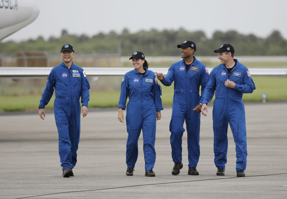 Astronaut Soichi Noguchi, of Japan, from left, NASA Astronauts Shannon Walker, Victor Glover and Michael Hopkins walk after arriving at Kennedy Space Center, Sunday, Nov. 8, 2020, in Cape Canaveral, Fla. The four astronauts will fly on the SpaceX Crew-1 mission to the International Space Station scheduled for launch on Nov. 14, 2020 (AP Photo/Terry Renna)