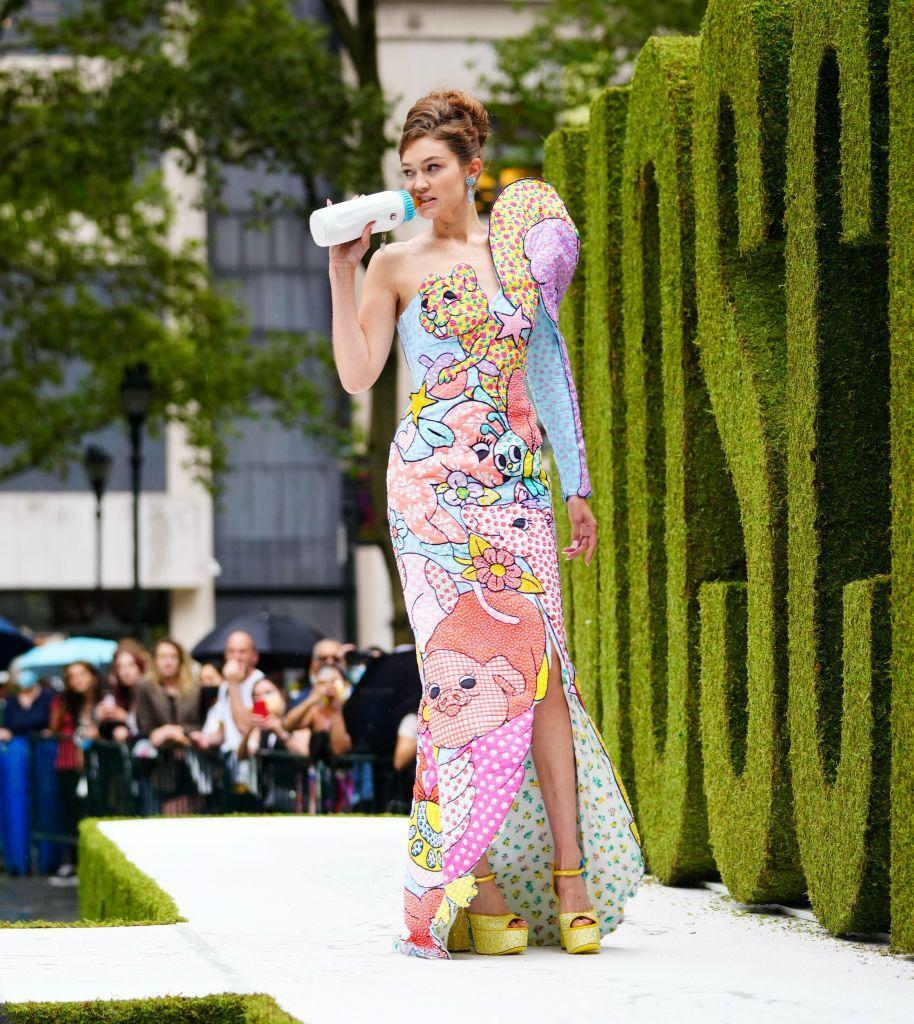 """<p>You can always count on Jeremy Scott for a tongue-in-cheek take on fashion week. The designer sent cartoon graphics (as he often does) down the runway for SS22, but it was Gigi gnawing on a baby bottle (<a href=""""https://www.elle.com/uk/life-and-culture/a35286743/gigi-hadid-baby-khai-name-meaning/"""" rel=""""nofollow noopener"""" target=""""_blank"""" data-ylk=""""slk:a year after giving birth to her daughter Khai"""" class=""""link rapid-noclick-resp"""">a year after giving birth to her daughter Khai</a>) that drew most of the attention.</p>"""