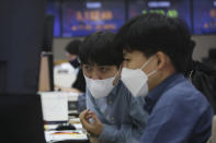 Currency traders wearing face masks watch monitors at the foreign exchange dealing room of the KEB Hana Bank headquarters in Seoul, South Korea, Tuesday, April 6, 2021. Asian shares were mixed Tuesday after a Wall Street rally that reflected some optimism about the economy recovering from the damage of the coronavirus pandemic. (AP Photo/Ahn Young-joon)