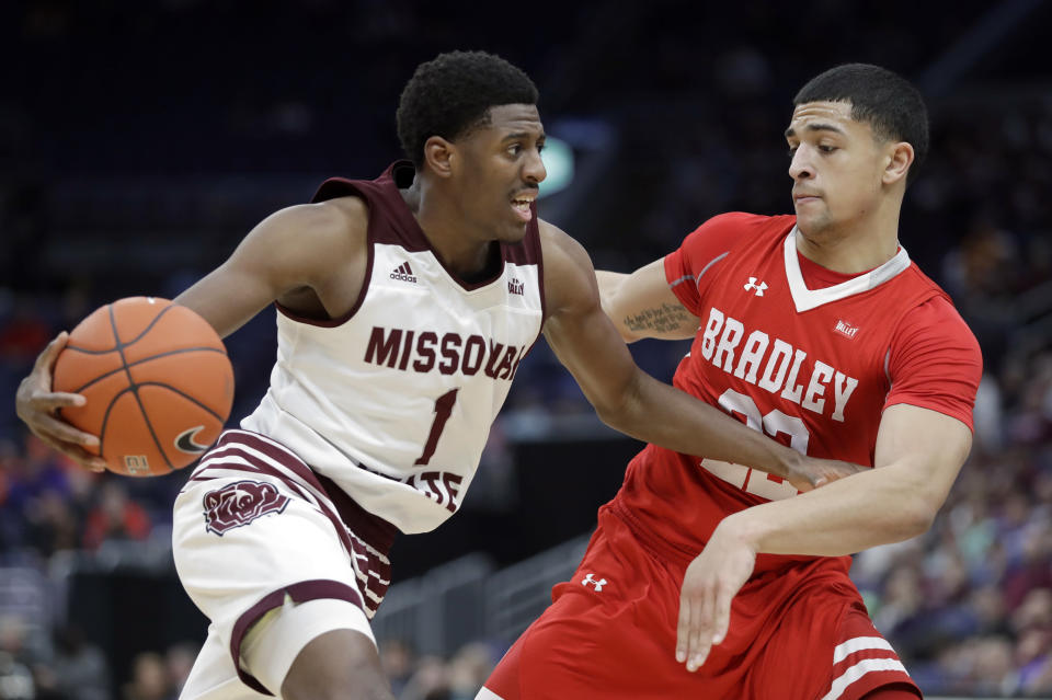 Missouri State's Keandre Cook (1) heads to the basket past Bradley's Ja'Shon Henry during the first half of an NCAA college basketball game in the quarterfinal round of the Missouri Valley Conference tournament, Friday, March 8, 2019, in St. Louis. (AP Photo/Jeff Roberson)