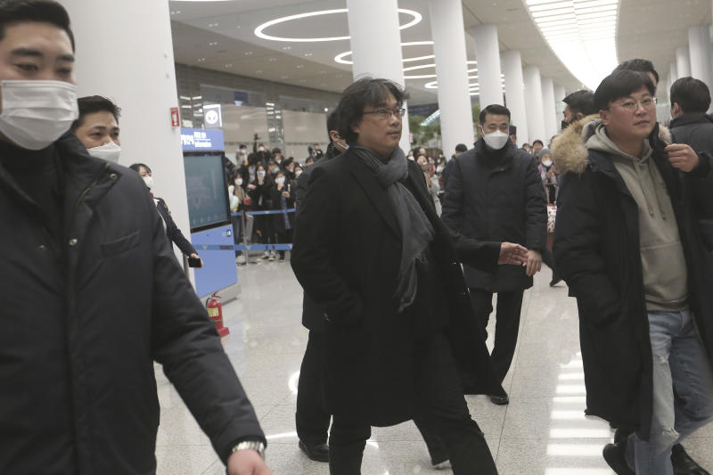 """South Korean director Bong Joon-ho, center, arrives at the Incheon International Airport in Incheon, South Korea, Sunday, Feb. 16, 2020. South Koreans are reveling in writer-director Bong's dark comic thriller, """"Parasite,"""" which won this year's Academy Awards for best film and best international feature. The movie itself, however, doesn't put the country in a particularly positive light. (AP Photo/Ahn Young-joon)"""