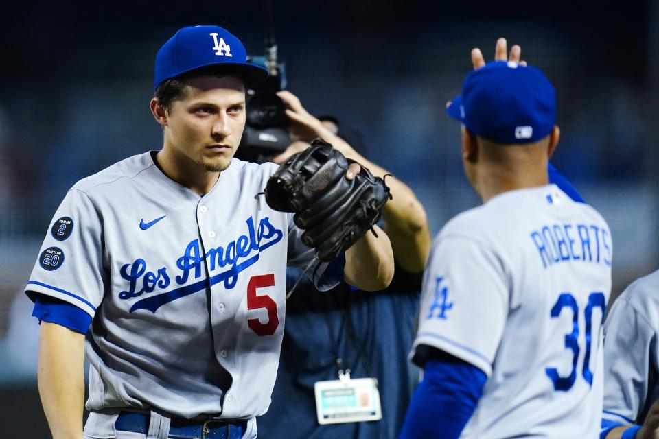 Los Angeles Dodgers shortstop Corey Seager (5) gets a high-five from Dodgers manager Dave Roberts (30) after a baseball game against the Arizona Diamondbacks, Sunday, Sept. 26, 2021, in Phoenix. The Dodgers defeated the Diamondbacks 3-0. (AP Photo/Ross D. Franklin)