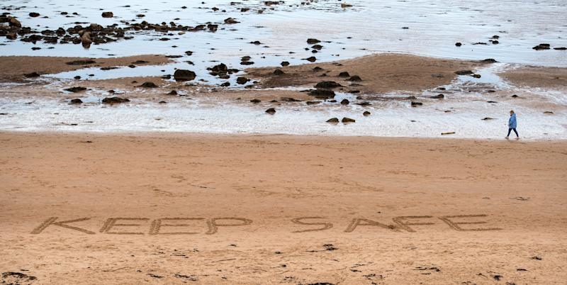 "A person walks past the words ""Stay Safe"", etched into the sand on the beach in Whitley Bay, north east England on April 30, 2020, as life in Britain continues during the nationwide lockdown to combat the novel coronavirus pandemic. - Britain is ""past the peak"" of its coronavirus outbreak, Prime Minister Boris Johnson said Thursday, despite recording another 674 deaths in the last 24 hours, taking the toll to 26,711. ""For the first time, we are past the peak of this disease... and we are on the downward slope,"" Johnson said in his first media briefing since returning to work following his own fight against the virus. (Photo by Oli SCARFF / AFP) (Photo by OLI SCARFF/AFP via Getty Images)"